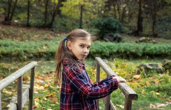 Portrait of a lovely little girl enjoys the beauty of an autumn in the park. Autumn mood..