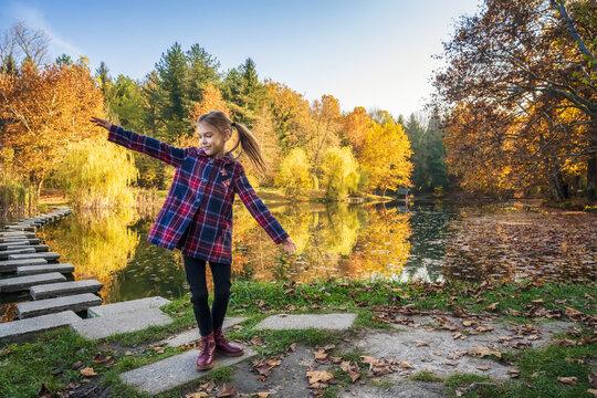Lovely little girl enjoys the beauty of an autumn near picturesque lake. Autumn mood...