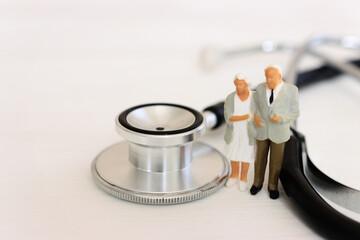 Obraz Miniature people near a stethoscope. Concept of insurance and health - fototapety do salonu