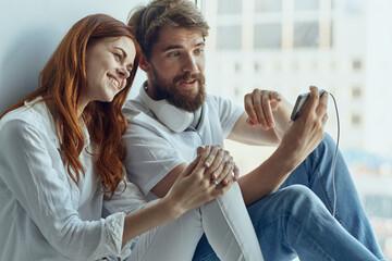 Obraz family chatting near the window romance joy technology - fototapety do salonu