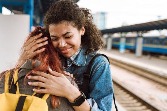 Multiracial two women hugging while saying goodbye at train station