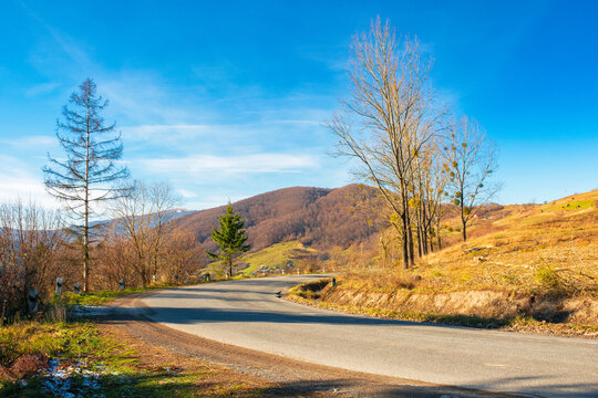 pass through carpathian mountains. trees along the road descending in to the valley of volovets, ukraine. sunny forenoon weather with clouds on the sky