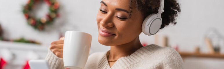 Obraz Happy african american woman in headphones holding cup while looking at smartphone during christmas at home, banner - fototapety do salonu