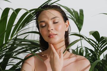 Fototapeta Young half-naked woman posing with plants on camera obraz