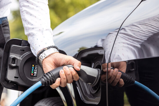Human hand is holding charging connect power supply plugged into an electric car