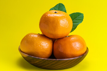 Fototapete - Ripe mandarin oranges with green leaves in wooden bowl.