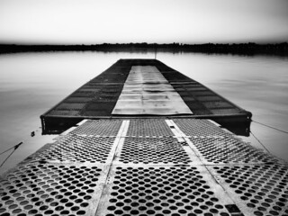 Metal pier with round holes. Evening or sunrise on a lake or river. Calm landscape. Rusting of metal structures. A pier for small cobbles and boats. Palic, Serbia. Travel, tourism, fishing. Monochrome