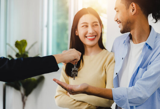 love couple talking with bank agent credit officer and receive house's key after success contract to buy new home, real estate concept