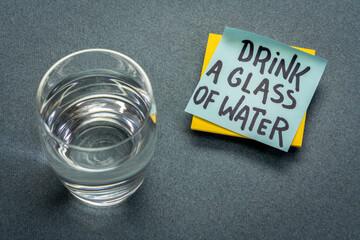 Obraz drink a glass of water - hydration reminder, handwriting on blue sticky note - fototapety do salonu