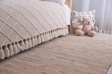 Fototapeta Stylish children's room interior with beige rug and bed obraz