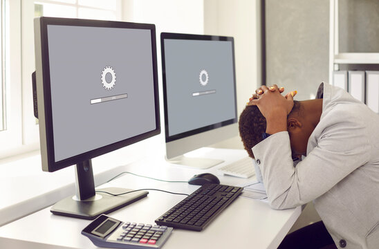 Unhappy, sad businesswoman or professional accountant sitting in front of multiple desktop computers, holding head in despair, waiting for new operating system to load or software update to install