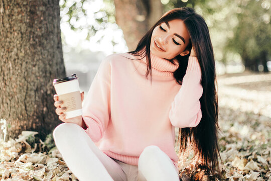 Beautiful woman drink coffee sitting in the park.