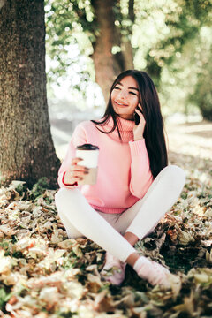 Beautiful woman drink coffee, using phone and sitting in the park.