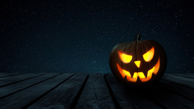 Scary glowing halloween pumpkin on a wooden old table with free space for design and text at night. Happy halloween concept.