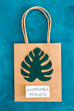 environmental awareness and consumer behaviour concept, Sustainable Product text on shopping bag with tropical green paper leaves on it