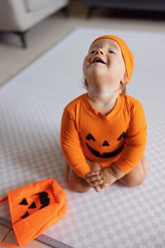 Cute caucasian infant baby Girl one year old in orange costume with pumpkin face at home. Happy Halloween concept
