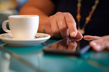 Fototapeta Close up on woman with white coffee cup on table, messaging with mobile phone. Sitting and enjoying tech and social obraz