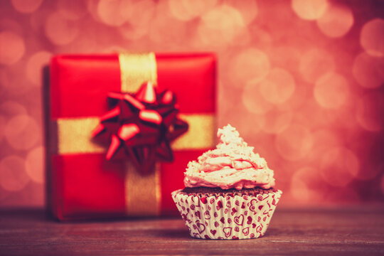 Cream cake and gifts on background.