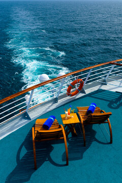 Sun loungers to enjoy the ocean views, with a cocktail table next to it on the ship's deck.