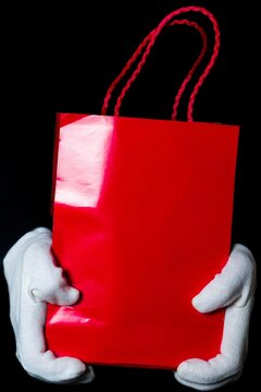 hands in white gloves hold a paper bag on a black background