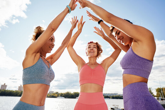 Group of diverse fit and active athletic female friends smiling and having fun together in the park before doing exercise