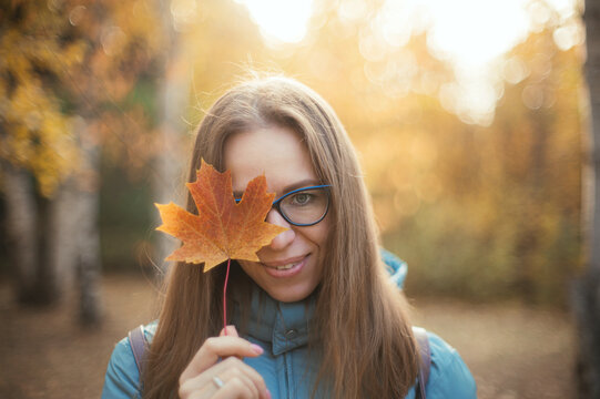 Autumn portrait of beautiful woman with maple leaves on fall nature background