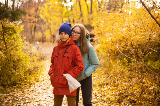 Autumn portrait of happy beautiful woman with her son on fall nature background. Shallow depth of field