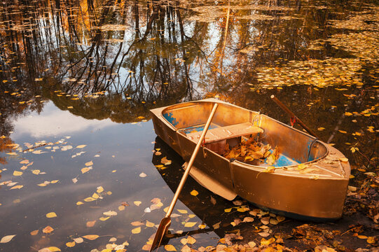 Golden wooden boat at beautiful autumn sunny day. Autumn peaceful landscape. with reflections