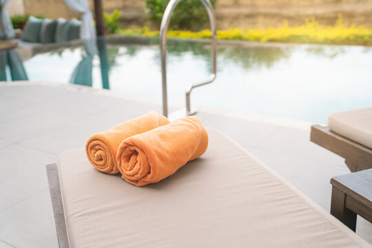 Folded orange towels on lounge chair by the  pool side, private pool villa, vacation