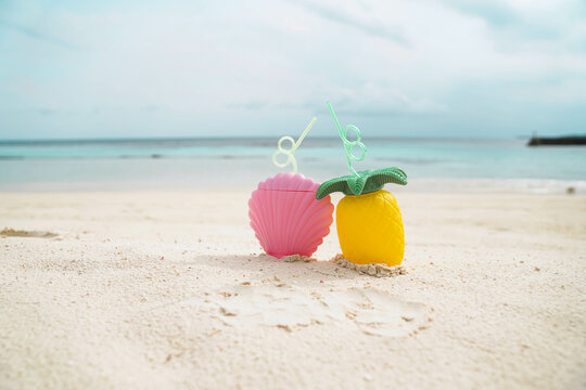 Exotic tropical summer drinks in pink shell shaped and pineapple shaped  bottle on the sandy beach background, Maldives