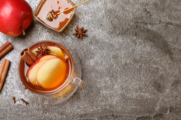 Fototapeta Aromatic hot mulled cider on grey table, flat lay. Space for text obraz