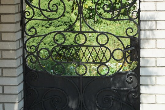 metal texture of black forged pattern of iron rods in the wall of the door on the street