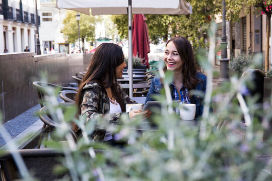 Happy young women having coffee sitting in outside cafe together in Madrid, Spain