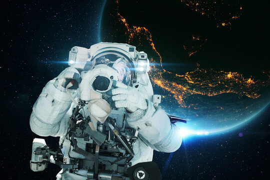 Spaceman astronaut with a camera takes a photo in open space with the blue planet earth and the lights of night cities. Space mission and space photographer concept
