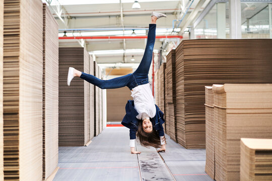 Excited businesswoman doing a handstand in factory warehouse