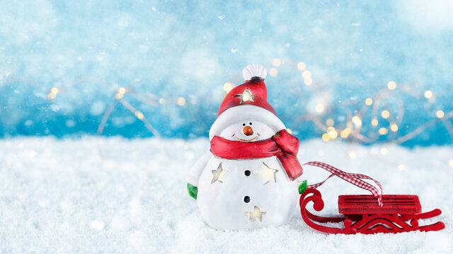 Happy snowman with red sleigh on snow.