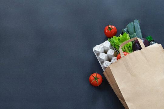Paper bag full of food on black background. Food delivery concept