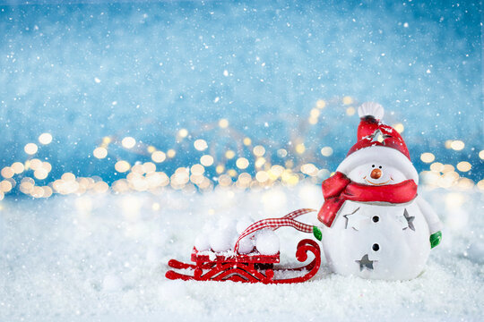 Happy snowman with red sleigh on snow with golden bokeh on background