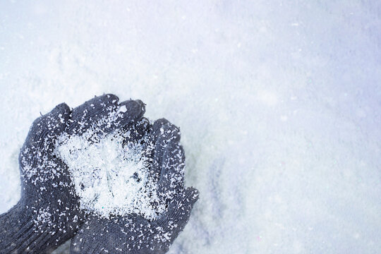 Hands in grey gloves holding snow and big crystal snowflake