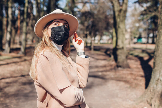 Stylish woman wears reusable mask outdoors during coronavirus covid-19 pandemic in empty spring park.