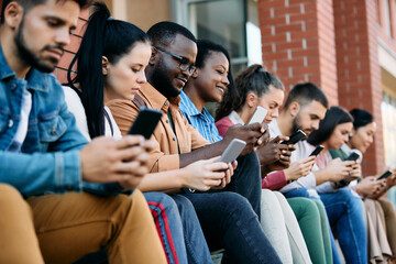 Fototapeta Multi-ethnic group of students use cell phones while relaxing outdoors. obraz