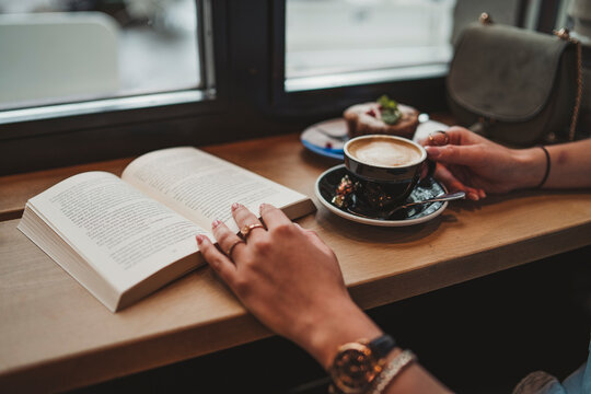 Close-up of woman with a book in a cafe