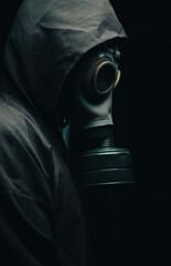 Obraz A scary man in a cloak wearing a gas mask. Dark background. Side view. - fototapety do salonu
