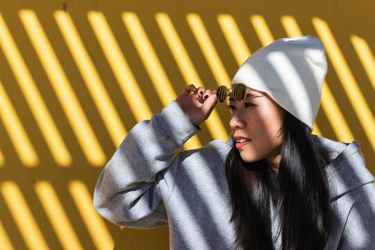 Woman removing sunglasses against yellow wall