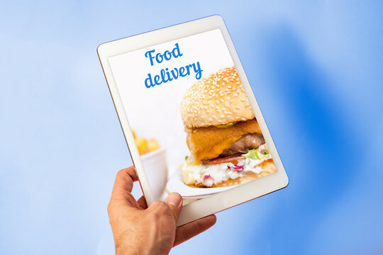 Food delivery concept, food ordering on internet via tablet. Man holding tablet on blue background