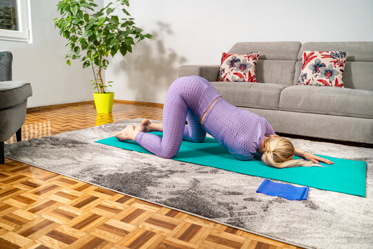 Attractive blonde woman stretching arms and shoulders on yoga mat in her home on the floor