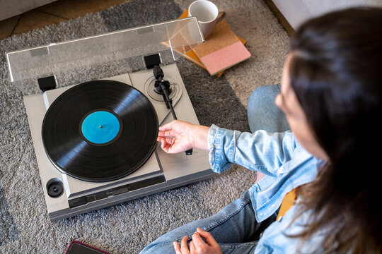 Woman playing record while sitting on carpet at home