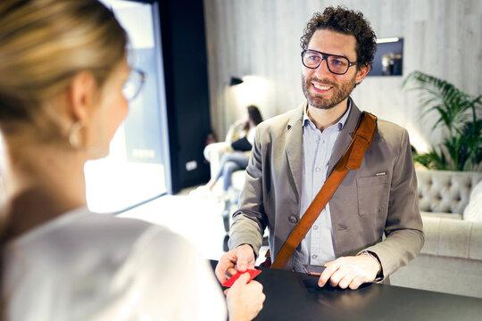 Smiling businessman handing over credit card at reception