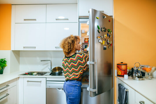 Young woman with curly hair opening the fridge in kitchen