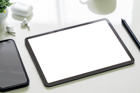 Mockup blank screen portable tablet and smartphone on white top table.